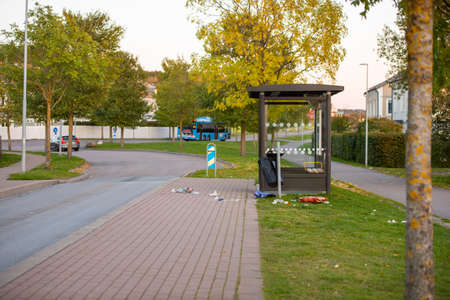 Mölndal, Sweden - October 18 2020: Garbage and crossed glass spread on the ground by a bus stop 新闻类图片