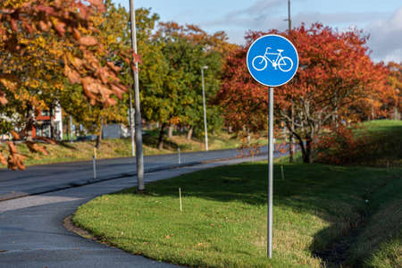 Bicycle path sign with autumn trees in the background