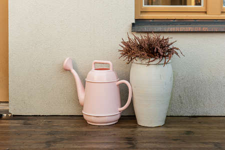 Watering can and a pot with heather by a house