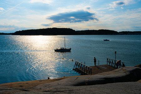 Motorboats passing cliffs and a bathing platform in summer Foto de archivo