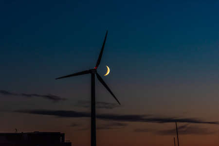 Waxing crescent moon passing behind a wind turbine at night 免版税图像