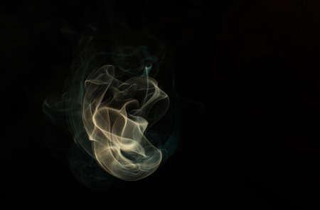 Yellow smoke on black background. 免版税图像