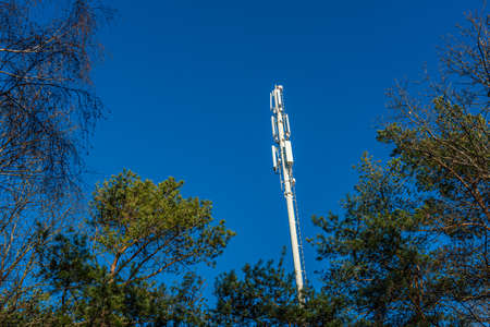 Mobile communications antenna tower in a forest