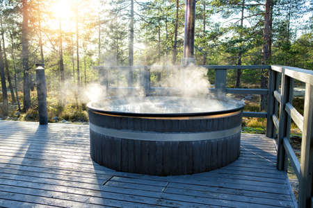 Modern big barrel outdoor hot tub in the middle of forest. The hot tub's soothing warm water relaxes muscles and eases tensions, so your worries can simply melt away. Foto de archivo