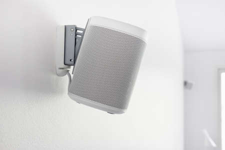 Wall mounted audio speaker on a white background.