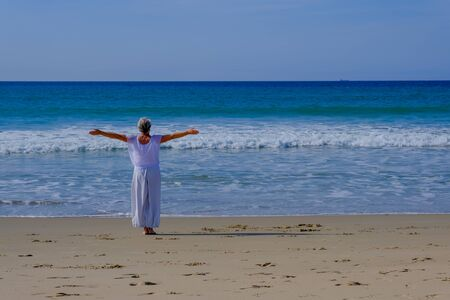 Senior woman with gray hair wearing a white dress and doing yoga and qi gong on the beach of Tarifa, Andalucia. Spain