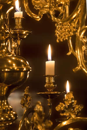 Candle in a shiny brass chandelier photo