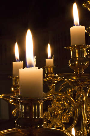 lit candle: Candles in a shiny brass chandelier Stock Photo