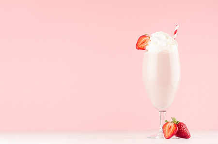 Pink fresh shake in graceful glass with strawberry, whipped cream and straw on pink background. Reklamní fotografie