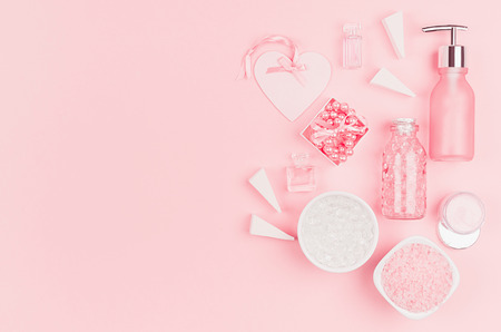 Natural skin care products, accessories for bathroom - cream, salt, essential oil, soap, perfume, pearls, gift, box, bottles, heart, bowl on pink background.