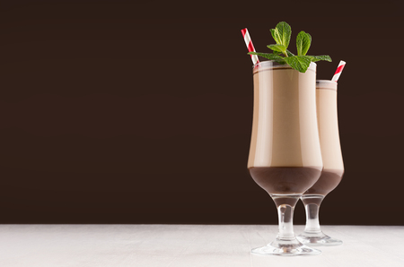 Luxury sweet chocolate milkshake in wineglass with fresh green mint and red striped straw on dark brown background, copy space.
