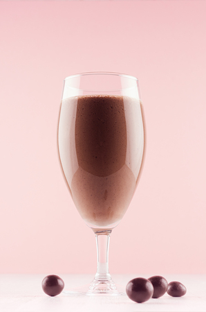 Chocolate milkshake in elegance glass with chocolate candies on white wooden table and pastel light pink wall, vertical.