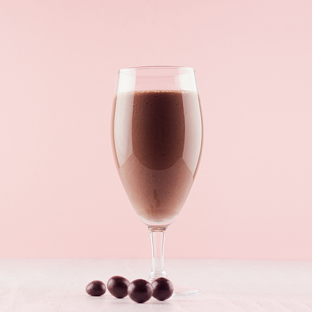 Healthy fresh chocolate smoothie with round brown sweety on pastel pink background, square.