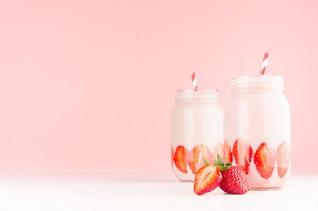 Bebidas de leche saludables de primavera con fresa madura cortada, pajitas de rayas rojas sobre fondo rosa pastel suave, mesa de madera blanca, espacio de copia.