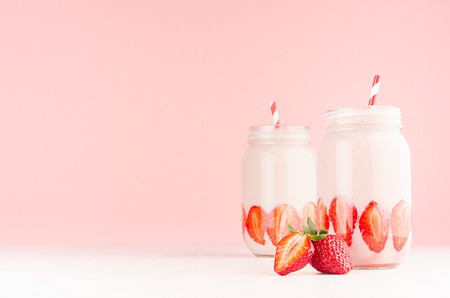 Spring healthy milk beverages with cut ripe strawberry, red striped straws on gentle pastel pink background, white wood table, copy space.