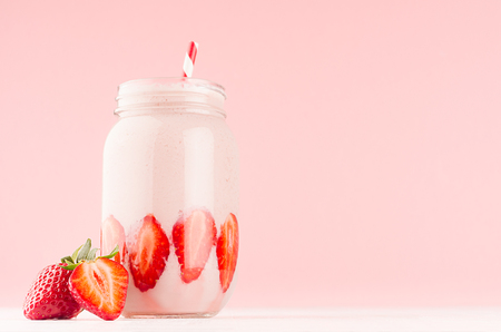 Fresh strawberry milk dessert for breakfast in jar with ripe berry, straw on pastel pink wall and white wooden table, closeup.
