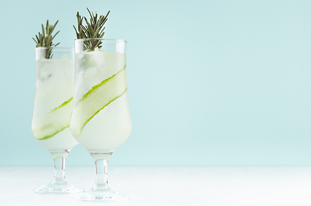 Fresh cool lemonade of cucumber with ice cubes, rosemary, lime in two wineglasses on white and pastel green background, copy space.