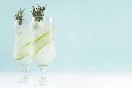 Frische kühle Gurkenlimonade mit Eiswürfeln, Rosmarin, Limette in zwei Weingläsern auf weißem und pastellgrünem Hintergrund, Kopierraum.