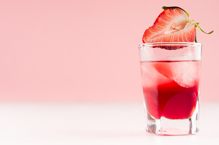 Exquisite cold red alcoholic liquor with ice cubes and strawberry slice in shot glass closeup on white wood table and pastel pink wall, copy space.