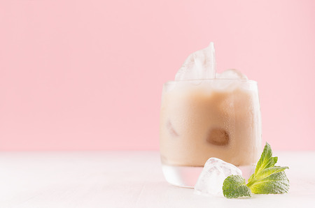 Creamy cold fresh beverage in misted glass with ice cubes, green mint and striped straw in modern light pink interior, copy space.