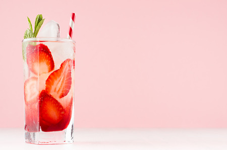 Homemade strawberry lemonade with slices, ice cubes, mint and straw in wet transparent glass in elegant soft light pink interior.