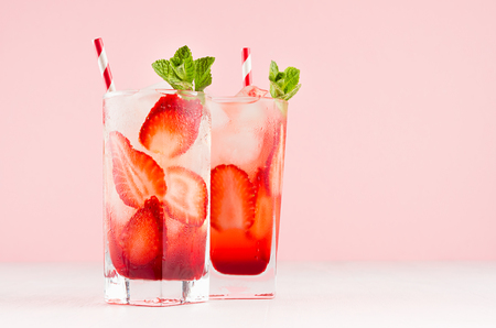 Cold tropical strawberry juices in misted glass with sliced berries, mint, ice cubes, straw on pastel pink background, white wooden table. Stock Photo