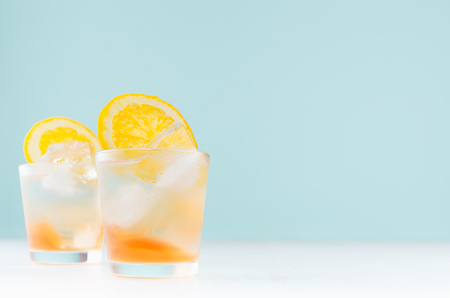 Summer fresh alcoholic drinks with oranges liquor, ice cubes in shot glass on blue wall, copy space.