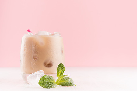 Sweet refreshing creamy alcoholic drink in glass with ice cube, green mint and straw in modern light pink interior on white wood table, closeup, copy space.