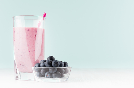 Detox milk violet drink with striped straw, ripe blueberry in bowl on soft pastel blue background and white wood table, copy space, closeup.