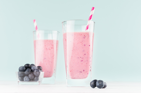 Pink smoothies with blueberries in bowl, striped straws in glass closeup on white wood table and pastel blue wall, copy space. Stock Photo