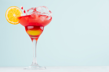 Summer homemade layered red and yellow drink with tequila orange, straw, ice cubes in glamour glass on green background.