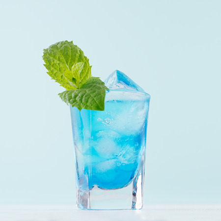 Exotic alcohol cold blue cocktail with curacao liquor, ice and green mint in rich wet shot glass on soft light pastel green background.