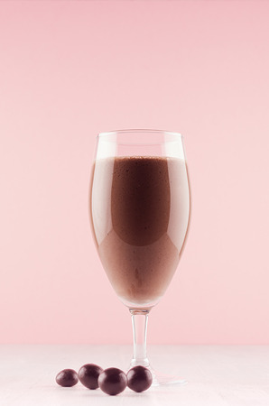 Exquisite light milk chocolate dessert with chocolate balls, whipped cream, red straw on modern elegant pink color background, vertical. Imagens