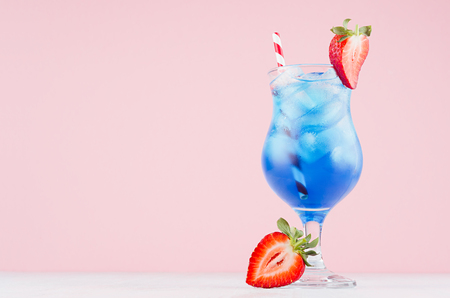 Fresh alcohol blue cocktail with curacao liquor, strawberry slice, ice cubes, red striped straw in misted glass on pink background. 版權商用圖片