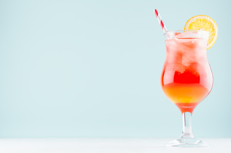 Summer cold alcohol striped cocktail with oranges juice, straw, ice cubes in luxury glass on pastel blue background, copy space.