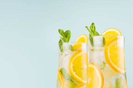 Healthy fresh oranges cocktail with sliced fruit, ice cubes, green mint on elegant soft blue color wall, closeup, top section, edge. 版權商用圖片