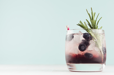 Fresh cold fruit cocktail in elegant glass with ice cubes, blueberry, rosemary, straw on pastel mint color background and white wood table, copy space.