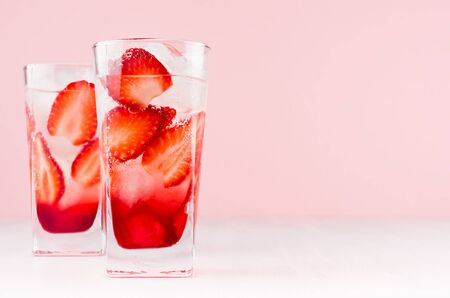 Refreshing strawberry drink with slices berry, ice cubes on soft light pastel pink background, copy space.