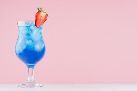 Tropical fresh blue drink with curacao, ice cubes, strawberry in exquisite misted wineglass on pastel pink wall, white table. 版權商用圖片