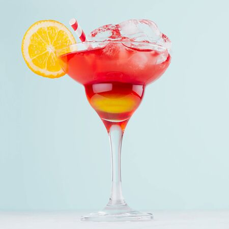 Bright layered red and yellow alcohol cocktail with oranges slice, straw, ice in wineglass on soft light pastel blue background, square.