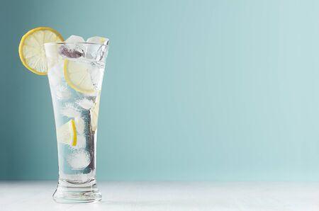 Frostige transparente Limonade mit Zitronenscheiben, Eiswürfeln und Mineralwasser in elegantem Glas auf weißem Holztisch, mintfarbene Wand.