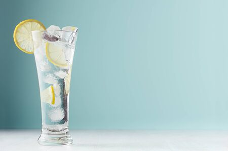 Frosty transparent lemonade with lemon slices, ice cubes and mineral water in elegant glass on white wood table, mint color wall. Stockfoto