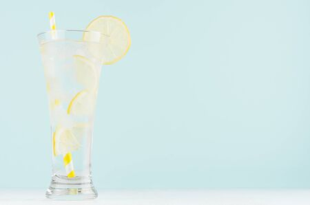 Homemade diet transparent lemonade with lemon, ice cubes, soda, yellow striped straw in misted glass on white wood table, pastel green color background. Stock Photo