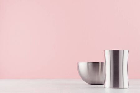 Fashioned home interior with rounded polished steel vases different form on white wood table and pastel pink wall. Banco de Imagens