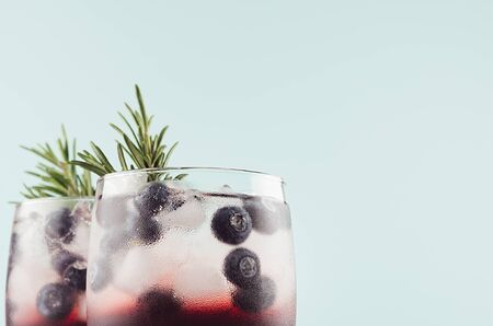 Tropical alcoholic shots of sweet berry liquor with ice cubes, blueberry, rosemary on pastel soft light green background, closeup, top section. 스톡 콘텐츠