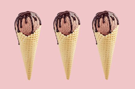 Set of three brown ice cream in crisp waffle cones with chocolate sauce on pastel pink background, mock up.