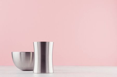 Simplicity elegant home decor with silver elegant glossy bowl and vase on white wood board and soft light pink background.