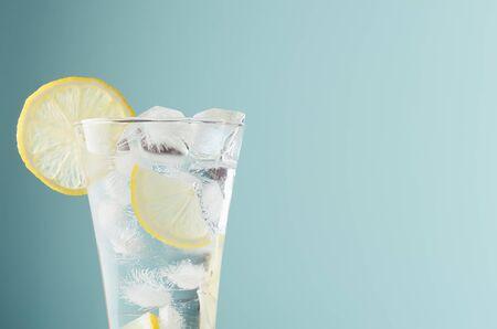 Gesundes frisches Tonic mit Zitrone, Eiswürfeln, Soda in Nebelglas auf pastellgrünem Hintergrund, Nahaufnahme, Hälfte, Details, Spitze.