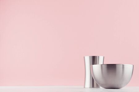 Minimalistic home decoration - glossy shine steel vases different shape on white wood board and pastel pink background.
