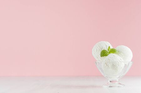Tasty fresh creamy ice cream in glass bowl with green mint on white wooden table and soft light pastel pink background.